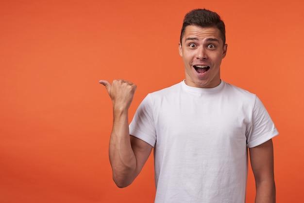 Geagiteerd jonge mooie bruinharige man die hand omhoog houdt terwijl hij opzij toont en verbaasd naar de camera kijkt met geopende mond, geïsoleerd op oranje achtergrond