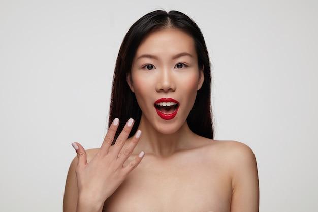 Geagiteerd jonge mooie donkerharige vrouw met feestelijke make-up met brede mond geopend en emotioneel verhogen haar hand, geïsoleerd over witte muur