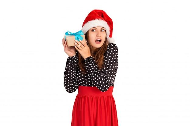 Gealarmeerd meisje luistert met haar geschenk naar wat er in de doos zit. geïsoleerd op wit. vakantie