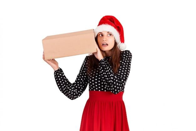 Gealarmeerd meisje met haar cadeau luistert naar wat er in de doos aanwezig is, geïsoleerd op wit,