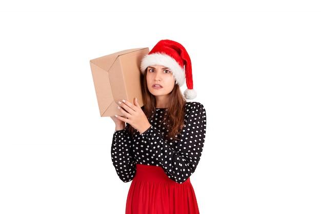 Gealarmeerd meisje met haar cadeau luistert naar wat er in de doos zit, geïsoleerd op wit,