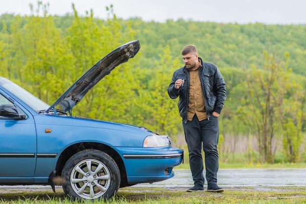 Gealarmeerde bestuurder probeert de auto te repareren