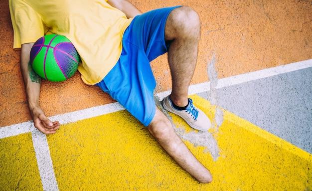 Geamputeerde jonge jongen die basketbal speelt in het park en sport maakt. concept over handicaps en volharding