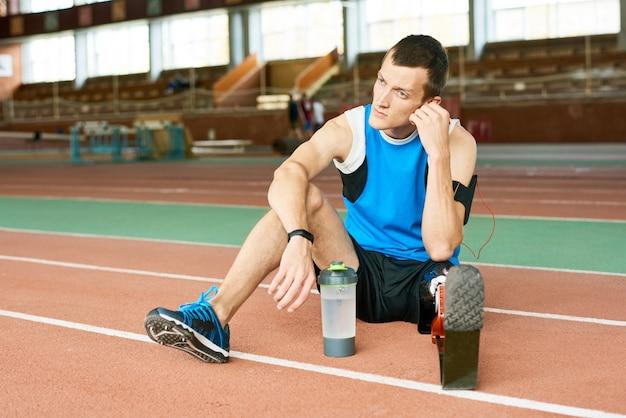 Geamputeerde sportman rust op de atletiekbaan