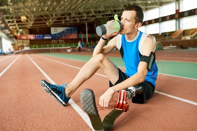 Geamputeerde sportman zittend op stadion track