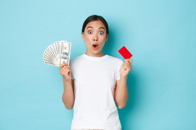 Geamuseerd aziatisch meisje in wit casual t-shirt hijgend, ontdekte geweldige prijzen, kortingsaanbiedingen in de winkel, met zowel creditcard als contant geld, lichtblauwe muur