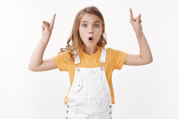 Geamuseerd behoorlijk opgewonden blond meisje, klein kind dat je iets geweldigs laat zien, handen omhoog, wijzend op de bovenste kopieerruimte, pruilend staren verbaasd, zeg wow opgewonden, leg ongelooflijke fantastische promo uit