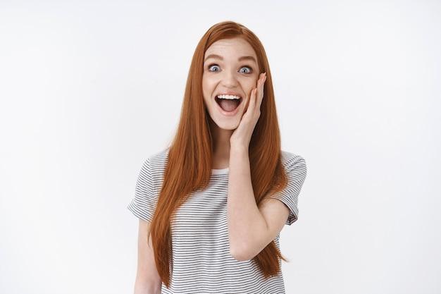 Geamuseerd blij vrolijk knap vermaakt roodharig meisje juichen aanraking wang verrast verwijden ogen glimlachen verbaasd krijgen goed nieuws beste geweldige dag ooit, staande witte muur