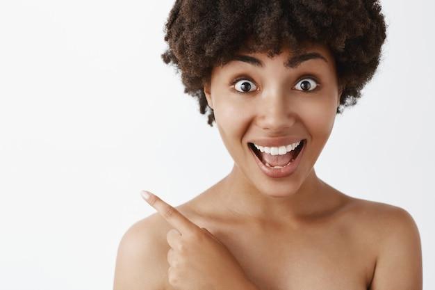 Geamuseerd en opgewonden afro-amerikaans vrouwelijk model met krullend kapsel naakt met schone huid, wijzend naar de linkerbovenhoek, vrolijk glimlachend, onder de indruk en tevreden met het product