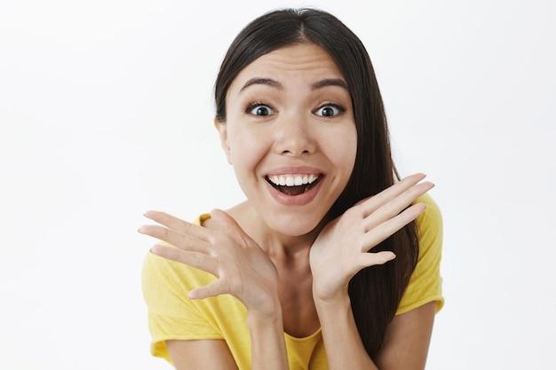 Geamuseerd en opgewonden gelukkig enthousiaste vrouw met donker haar in geel t-shirt met palmen in de buurt van gezicht