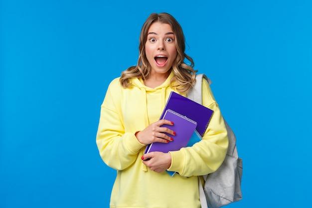 Geamuseerd en opgewonden opgewonden mooi blond meisje in gele hoodie, hijgend en verbaasd kijkend als ze goed nieuws hoort, notitieboekjes vasthoudt en rugzak naar school draagt, roddelend,