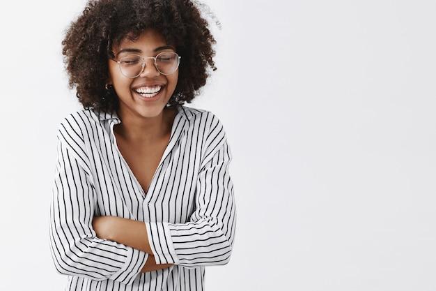 Geamuseerd en zorgeloos aantrekkelijke afro-amerikaanse vrouw in gestreepte blouse en glazen ogen sluiten hardop lachen en hand in hand op borst ogen met plezier sluiten