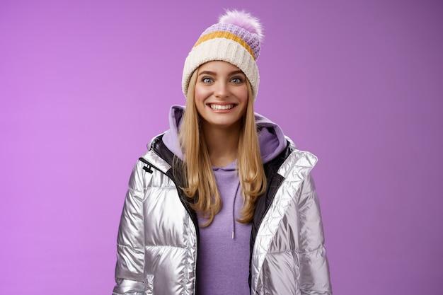Geamuseerd gefascineerd aantrekkelijk opgewonden blonde vrouw stepping ski's eerste keer verleiding voelen sensatie vreugdevol glimlachen ogen wijd onder de indruk kan niet wachten leren snowboarden staande zilveren jas.