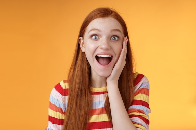 Geamuseerd, gelukkig lachend, goed uitziende roodharige vrouw die vrolijk schreeuwt, raakt de wang verbaasd aan en ontvangt goed perfect nieuws triomfantelijk opgewonden gevoel kijk opgewonden camera, staande oranje achtergrond.