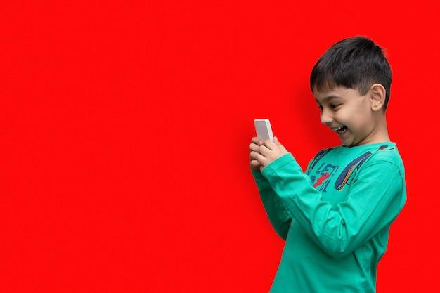 Geamuseerd jong kind dat spelletjes speelt op smartphone - poseren in studio