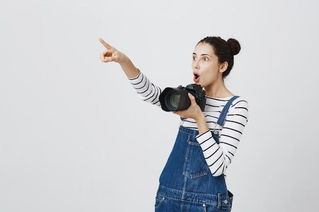 Geamuseerd mooi meisje wijst verbaasd linksboven en houdt de camera vast en neemt foto's