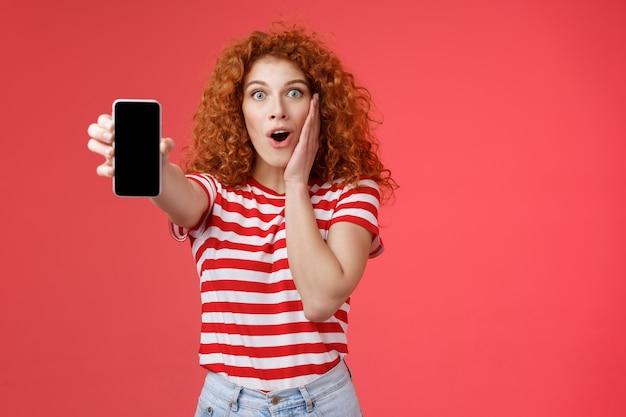 Geamuseerd onder de indruk roodharige knap krullend opgewonden meisje delen geweldige sociale media pagina tonen smartphone scherm verbaasd aanraking wang opgewonden getroffen geweldige app rode achtergrond.