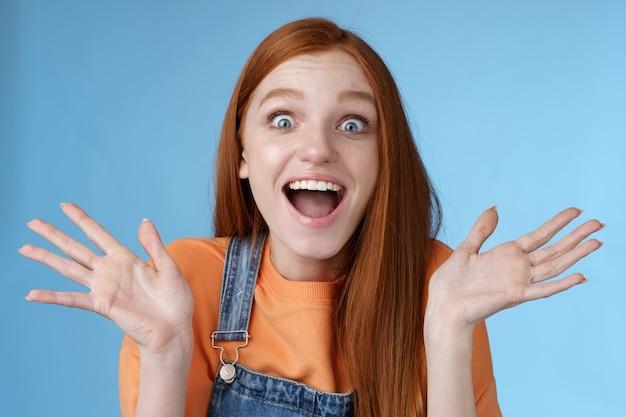 Geamuseerd sprakeloos verrast verbaasd roodharig meisje hoort opwindend positief nieuws glimlachend graag brede ogen opgewonden opgeheven hand triomferend win loterij vieren overwinningssucces, blauwe achtergrond.