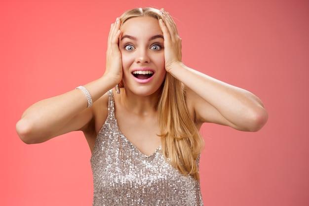 Geamuseerd verrast opgewonden jonge blonde aantrekkelijke vrouw in zilveren glinsterende stijlvolle jurk houdt hoofd handen verwijd ogen sprakeloos kijken camera ongelooflijke sensatie fan zie beroemd persoon, rode achtergrond.