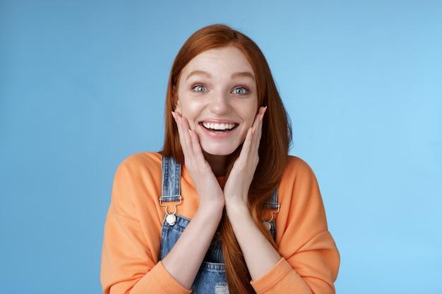 Geamuseerd vrolijk verrast jonge aantrekkelijke dochter auto verjaardag aanwezig staand verbaasd sprakeloos blik blij camera aanraking wangen opwinding glimlachend breed blauwe achtergrond