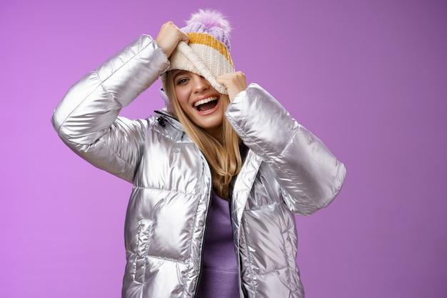 Geamuseerd zorgeloos gelukkig lachend speelse aantrekkelijke vrouw plezier lachen vreugdevol trekken hoed gezicht verbergen gluren een oog camera grijnzend grinniken dwaas rond veel plezier, paarse achtergrond.