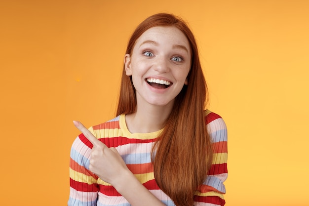 Geamuseerd zorgeloos opgewonden emotionele roodharige vrouwelijke fan dol op pratende favoriete film wijzend linkerbovenhoek gefascineerd glimlachen breed gelukkig opgetogen bijwonen ongelooflijk feest, oranje achtergrond.