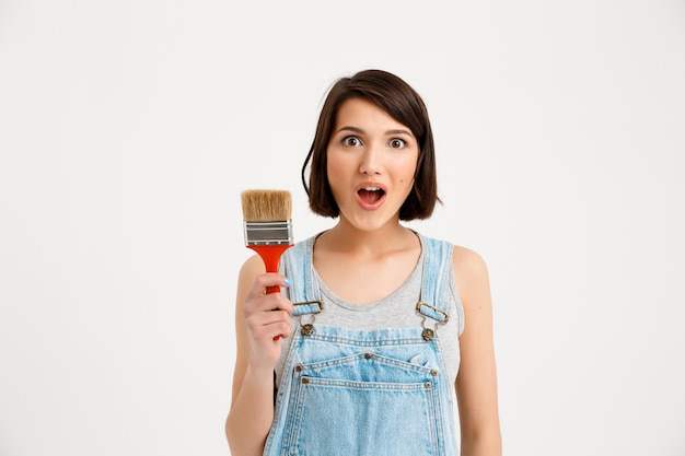 Geamuseerde creatieve vrouw met het schilderen van borstel