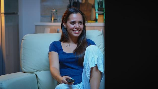 Geamuseerde dame die 's nachts op de bank naar tv-programma's kijkt. jonge, opgewonden, alleenstaande vrouw die van de avond geniet terwijl ze op een comfortabele bank zit, gekleed in een pyjama en popcorn eet voor de televisie