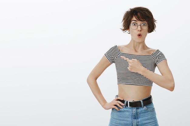 Geamuseerde en geïnteresseerde vrouw die vraag stelt over product, wijzende vinger linksboven