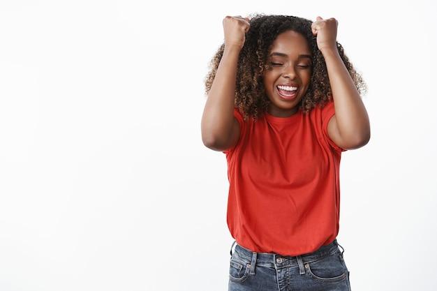 Geamuseerde en gelukkige opgewonden vrouw die van vreugde en triomf springt en gebalde vuisten opheft in de buurt van het hoofd, de ogen sluit en glimlacht, zich vrolijk voelt als het vieren van de overwinning en het succesvol behalen van het doel