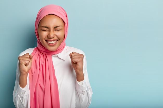 Geamuseerde gelukkige arabische vrouw heft gebalde vuisten, bereikt doel met succes, houdt de ogen dicht