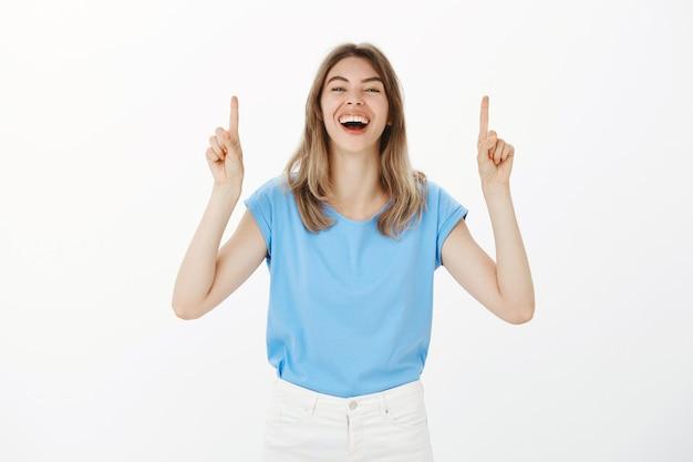 Geamuseerde gelukkige blonde vrouw lachend, wijzende vingers omhoog, aankondiging doen