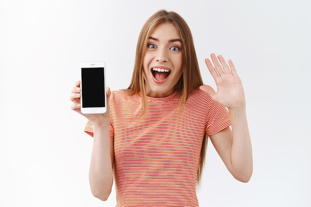 Geamuseerde jonge blanke vrouw in gestreept t-shirt die er vrolijk uitziet, smartphone vasthoudt, zwart mobiel display toont, met één hand zwaait, afscheid neemt van ex-vriend als zijn profiel, witte achtergrond ontvolgt