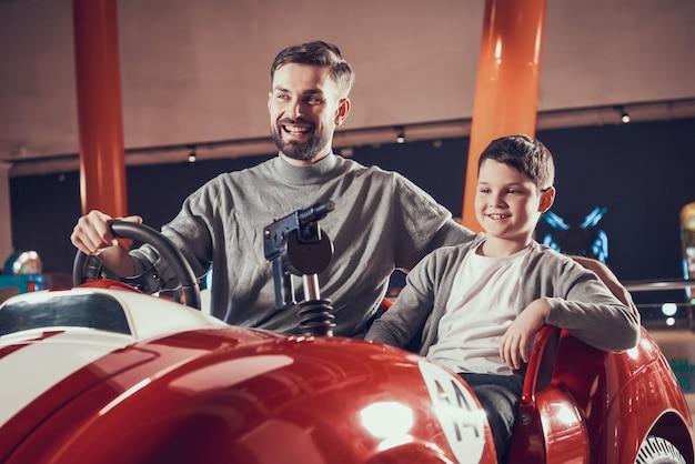 Geamuseerde lachende vader en zoon zittend op speelgoedauto
