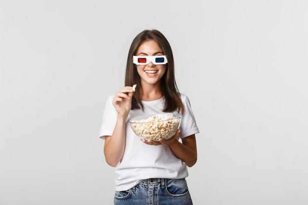 Geamuseerde mooie jonge vrouw in 3d-bril films of tv-series kijken, popcorn eten en opgewonden glimlachen.