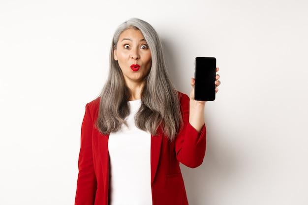 Geamuseerde senior vrouw in rode blazer, die er gefascineerd uitziet en een leeg smartphonescherm toont, staande op een witte achtergrond.