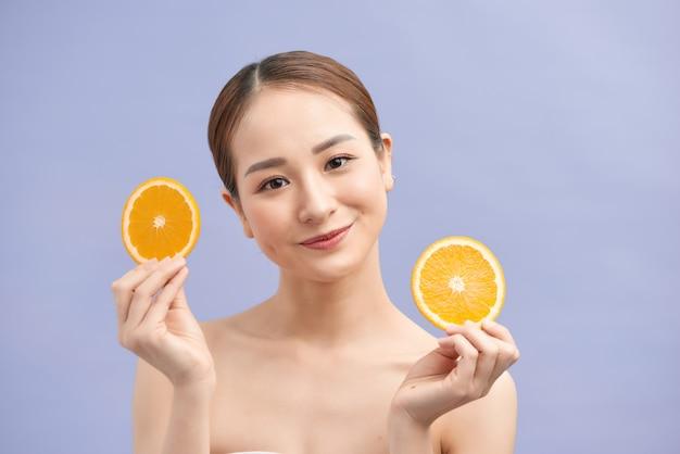 Geamuseerde verse aziatische vrouw die twee sinaasappelenplakken op violette muur houdt