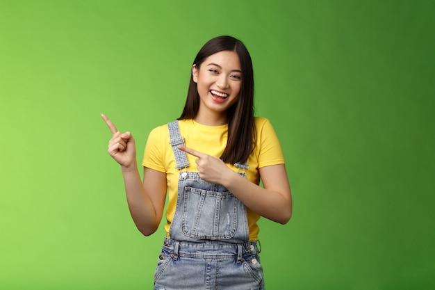 Geamuseerde vriendelijke gemakkelijke aziatische vrouw die plezier heeft, bespreekt grappige komedieprestaties die naar links wijzen...