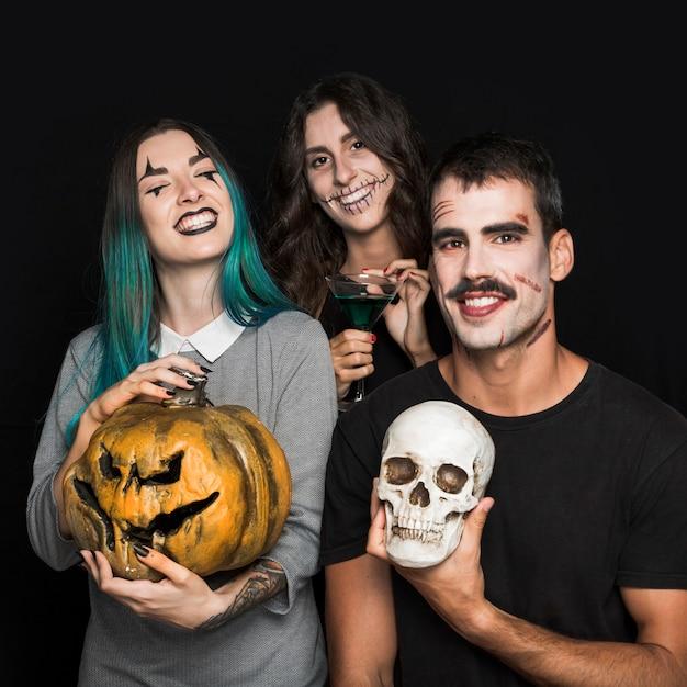 Geamuseerde vrienden met attributen van halloween