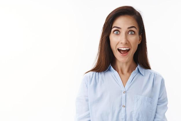 Geamuseerde vrolijke volwassen huisvrouw ziet er onder de indruk uit, open mond gefascineerd verrast, glimlachend opgewonden, neemt deel aan een interessant evenement, staart naar voren verwonderd enthousiast, witte muur