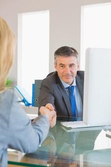 Geamuseerde zakenman die de hand van een geïnterviewde schudt