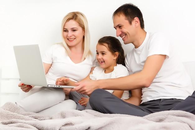 Geanimeerde familie die thuis online op bed ligt