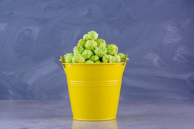 Gearomatiseerde popcorn opgestapeld in een gele emmer op marmeren achtergrond. hoge kwaliteit foto