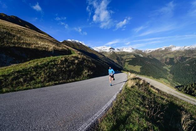 Geasfalteerde bergweg met eenzame loper in opleiding