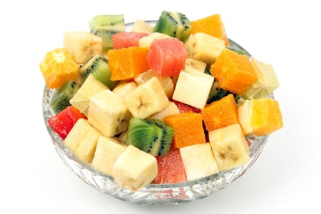 Geassorteerd fruit gehakt in blokjes op een bord op een witte achtergrond. nuttig vitaminevoer van fruit