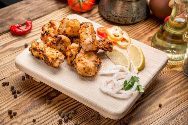 Geassorteerd heerlijk geroosterd vlees met groente op de witte lijst van de plaatpicknick voor familiebbq partij