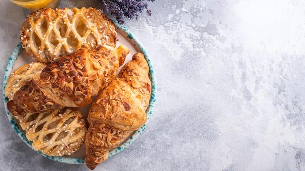 Geassorteerd van verse gebakjes en croissants op een plaat. bovenaanzicht