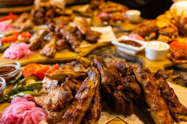 Geassorteerd vlees op een plaat close-up. verschillende soorten vlees en aardappelen in een hoop. voorgerecht op een groot bord met sauzen.
