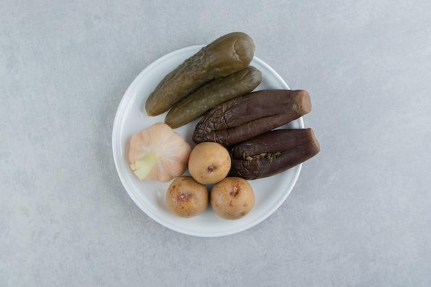 Geassorteerde augurken geplaatst op witte plaat.
