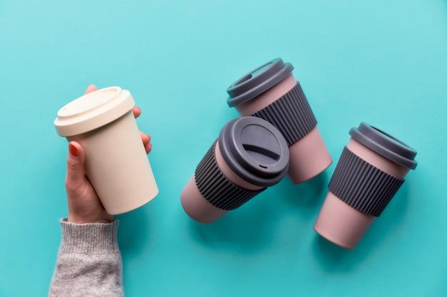 Geassorteerde bamboe reis herbruikbare koffie- of theekopjes of mags met siliconenisolatie.handen openen siliconen deksel op witte mok. milieuvriendelijke ideeën zonder afval voor een duurzame levensstijl met een lage impact.